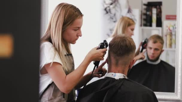 Stylist doing stylish haircut for client in barber shop