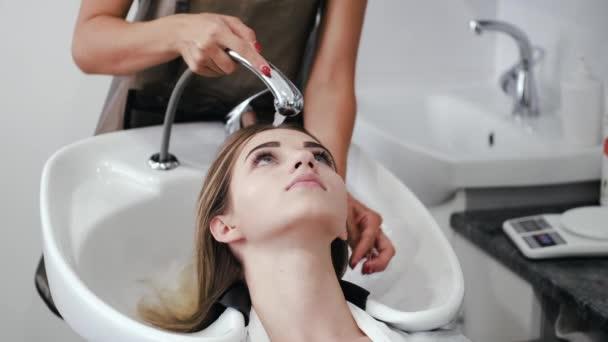 Kadeřník mytí dívky hlavu v bílém dřezu v salonu