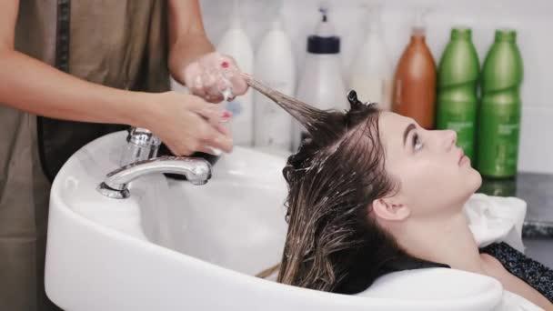 Kadeřník mytí ženy vlasy s šamponem v bílém dřezu