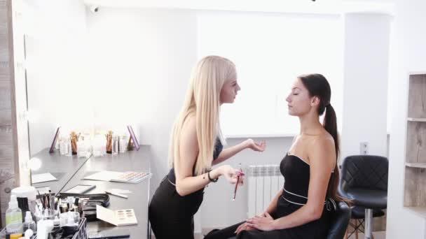Make-up umělec dělá make-up pro klienta brunetky v salonu