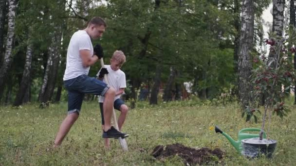 The family of father and son are making a place to plant a tree