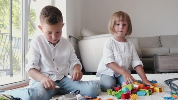 Erkek ve kız kardeş evde lego oynuyorlar.