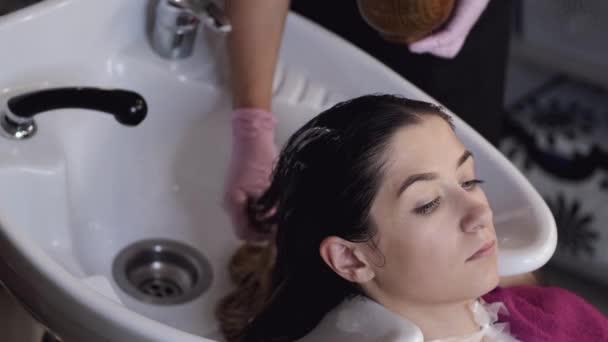 Stylista mytí klientů vlasy v umyvadle v salonu krásy