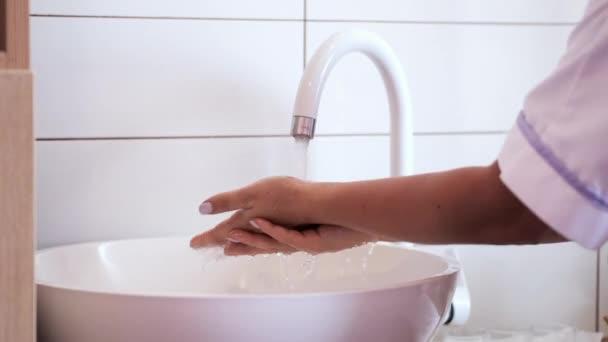 Kosmetolog provádí dezinfekci rukou před zákrokem v salonu