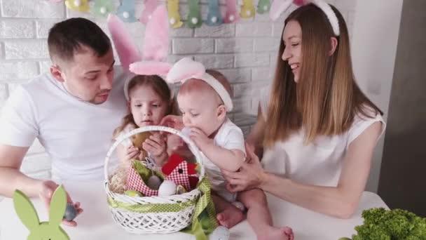 A család húsvétot ünnepel egy díszített konyhában.