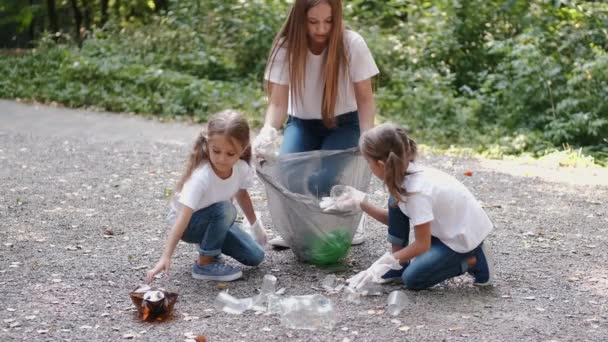 Woman and two little girls collecting rubbish in forest