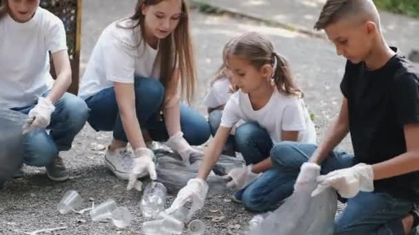 Young volunteer and children collecting garbage together in forest