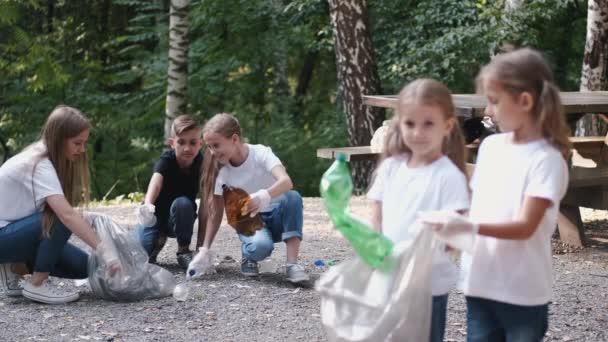 Gruppe von Kindern mit jungen Freiwilligen sammelt Müll im Wald