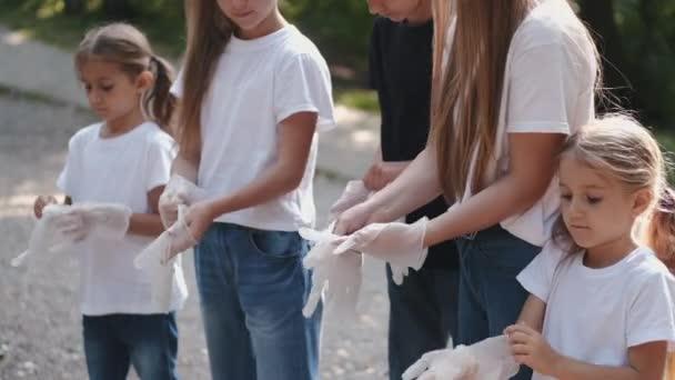 Gruppe von Kindern zieht Handschuhe an, bevor sie den Müll einsammelt