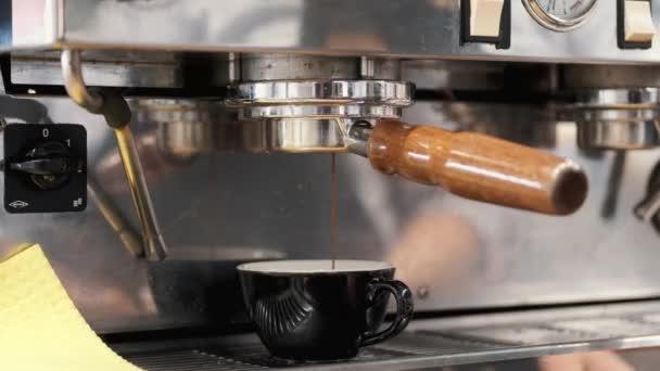 Az eszpresszó kávét gépből öntik egy kávésbögrébe.