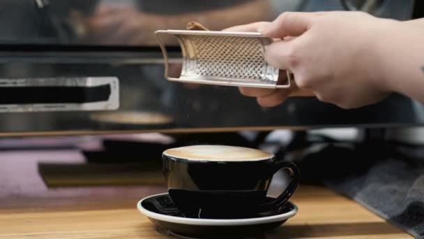 A barista egy mozipálcát csiszol egy kávésbögrén.