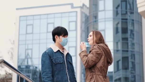 Eine Frau und ein Chinese tragen Schutzmasken