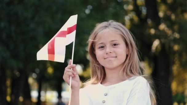 Portrét blonďaté dívky držící anglickou vlajku v parku