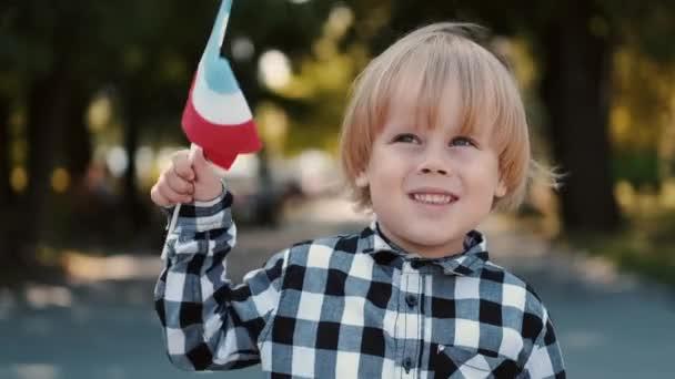 Blonďatý chlapec v kostkované košili s lucemburskou vlajkou