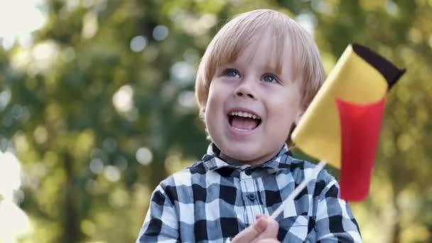 Portrét malého chlapce hrajícího si s belgickou vlajkou v parku
