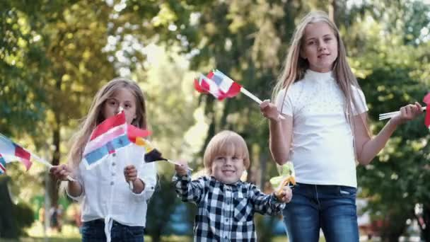 Children holding different flags having fun in park