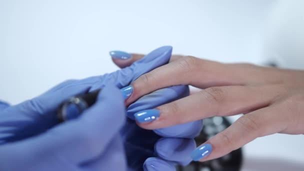Detailní záběr kosmetik ruce dělat modrou manikúru pro klienta