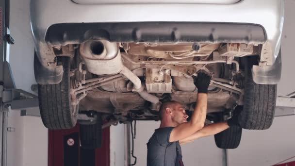 Mechanik v rukavicích pracující pod autem v servisním centru