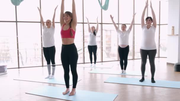 Frauen machen Dehnübungen in einem modernen Fitnessstudio mit einem Trainer