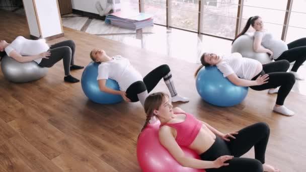 Europäische Frauen machen Nierenübungen mit Gymnastikbällen und Instruktor