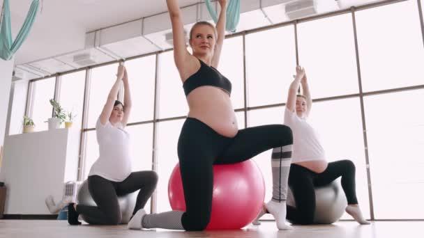 Schwangere machen in einem Fitnessstudio pränatale Übungen auf Fitnessbällen