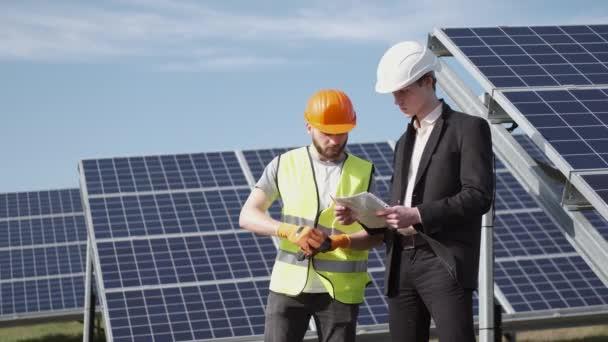 Ingenieur und Arbeiter diskutieren etwas in der Nähe von Solarbatterien