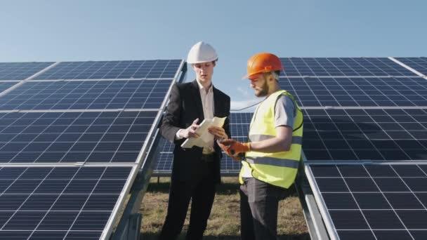 Podnikatel a pracovník jsou v solární elektrárně diskutovat o projektu