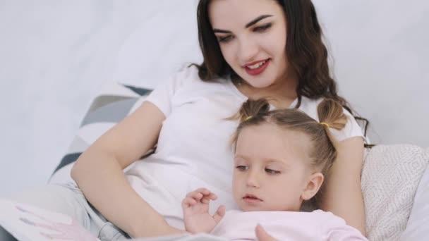 Krásná matka a batole dcera jsou v posteli objímání a čtení knihy