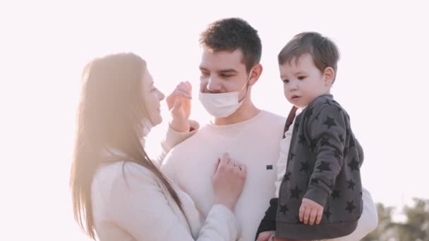 Young lovely woman and man with a son in masks are kissing outside