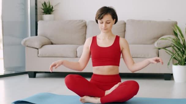 Frau im Fitnesskostüm macht morgendliche Yoga-Übungen auf einer Matte