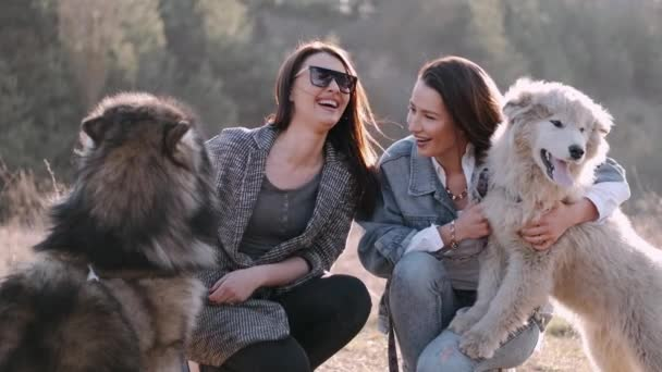 Young beautiful women are smiling and hugging with their fluffy cute dogs