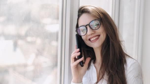 Hezká žena v brýlích volá u okna a usmívá se