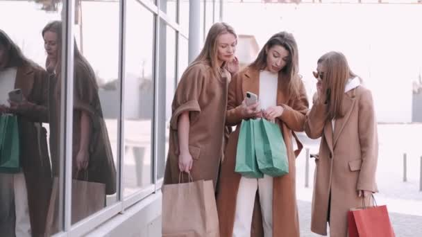 Pretty girls are checking shopping bags with clothes