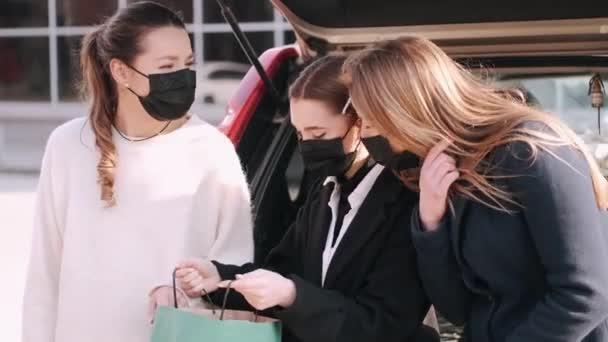 Drei maskierte Mädchen betrachten Einkaufstüten neben einem Auto