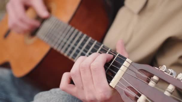 Oříznutý pohled na mužské ruce provádějící píseň na kytaru