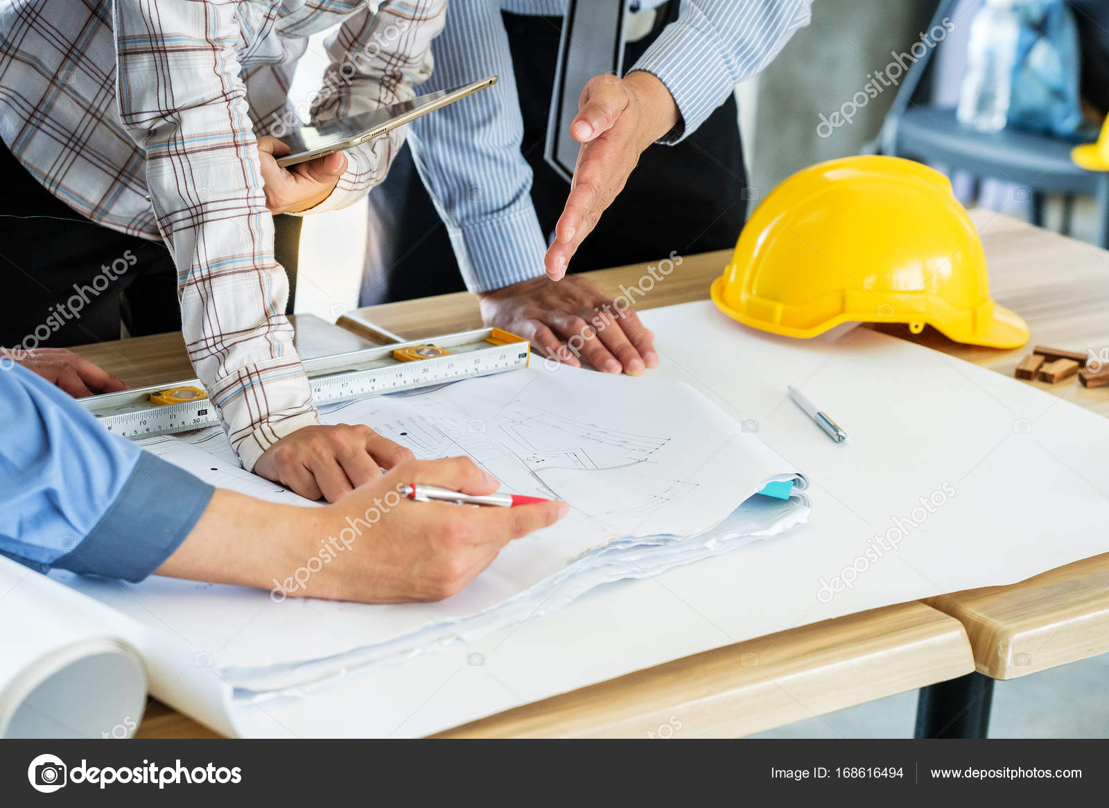 A group of engineers are looking at a blueprint for construction a group of engineers are looking at a blueprint for construction on the table photo by subinpumsom malvernweather Images