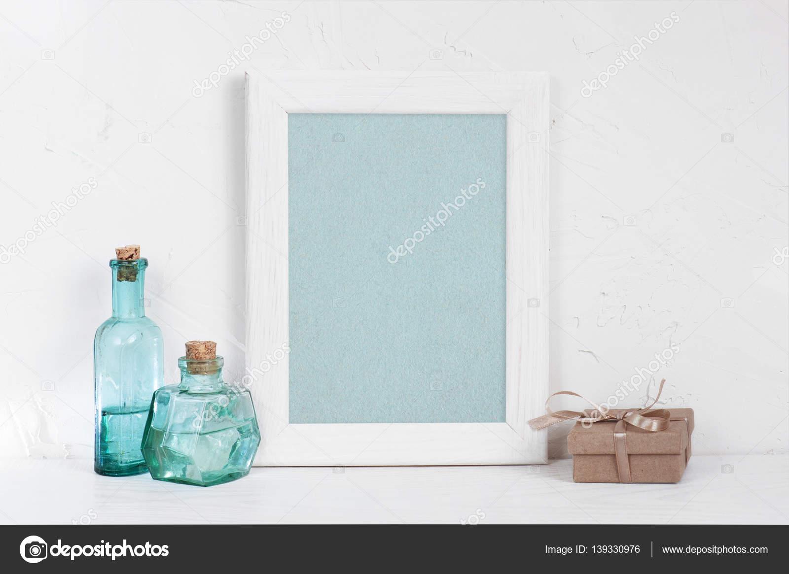 Marco blanco de madera vacía, botellas de vidrio azul y caja de ...
