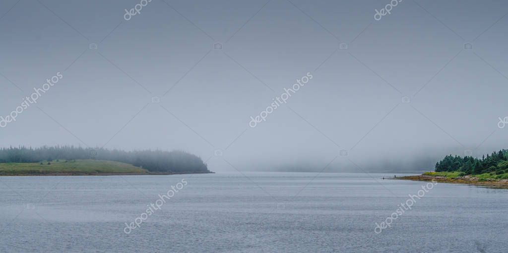 Two fishermen in Newfoundland fog at the shore of an inlet.