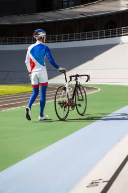 Racing cyclist on velodrome outdoor.