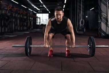 Muscular men lifting deadlift