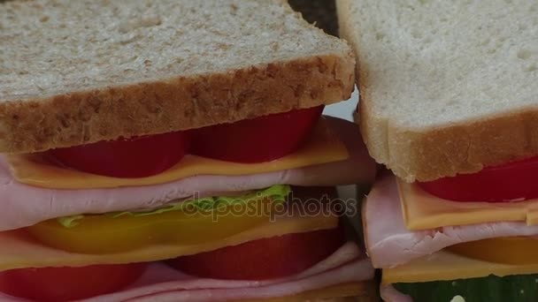 Close-up of two sandwiches with bacon, salami, prosciutto and fresh vegetables