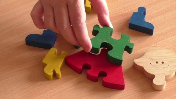 Ruce, které staví dřevěné puzzle