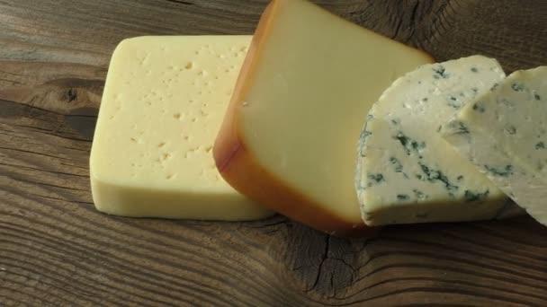Různé typy sýrů na dřevěný stůl