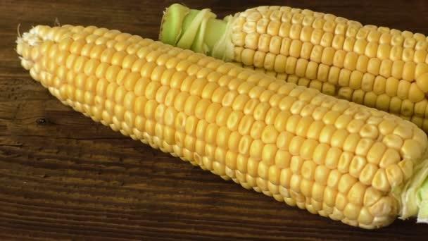 Dvě čerstvé kukuřice na palice na rustikální dřevěný stůl