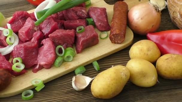 Vaření guláš s hovězím masem a zeleninou. Čerstvé syrové maso na prkénku