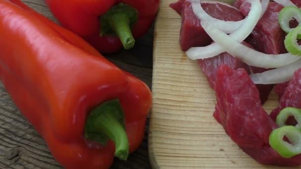 Čerstvé syrové sekané hovězí maso na dřevěném prkénku s čerstvou bio zeleninu, cibuli, česnek