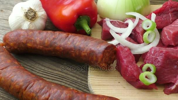 Suroviny pro guláš, guláš či polévku. Čerstvé syrové sekané hovězí maso na dřevěném prkénku s kořením a zeleninou