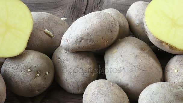 Brambory na dřevěné pozadí. Raw bio brambory ve slupce špinavé