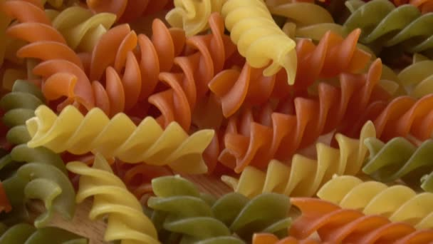 Uncooked three-colored italian pasta. Dried italian pasta on a wooden table.Colored natural pasta