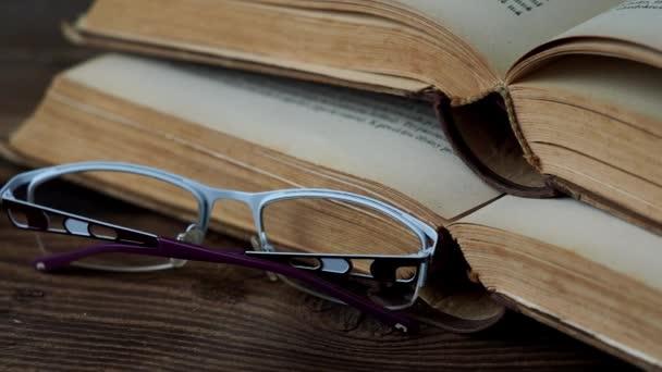 knihy a sklenice na dřevěném stole